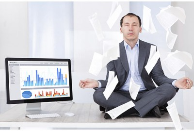 Full length of mid adult businessman meditating while documents falling over him by computer in office